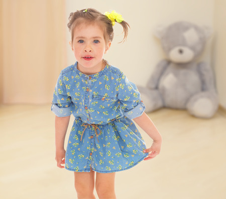 little girl in a blue short dress on a teddy bear photo