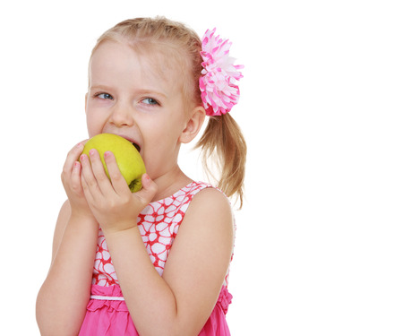 little girl biting a big yellow apple on white  Stock Photo