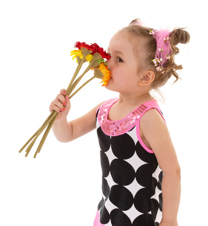 very young little girl smelling a beautiful bouquet of flowers.  Stock Photo
