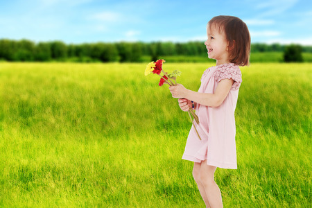 Girl with flowers in summer field. photo
