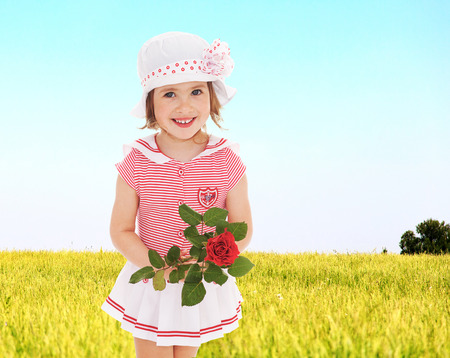 Cheerful girl with a rose in his hand is on the background of a summer meadow. photo