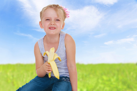 Girl with banana on nature background. photo