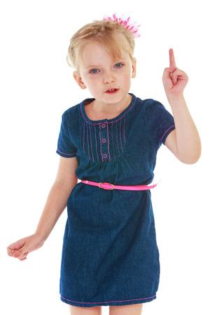threatens: Emotional girl in blue denim dress threatens finger. Stock Photo
