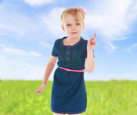 Emotional girl in blue denim dress threatens finger.spring season,fun outdoors,happy childhood,sweet child having fun outdoor,smiling toddler portrait photo