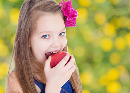 A girl eats an Apple in nature.spring season,fun outdoors,happy childhood,sweet child having fun outdoor,smiling toddler portrait photo