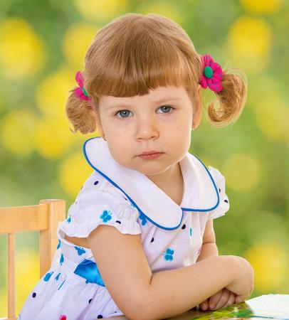 Sad girl in kindergarten.spring season,fun outdoors,happy childhood,sweet child having fun outdoor,smiling toddler portrait photo