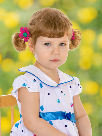 Portrait of a serious girl with ponytails.spring season,fun outdoors,happy childhood,sweet child having fun outdoor,smiling toddler portrait photo