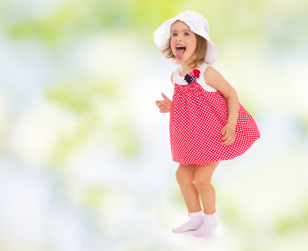 hurray: girl in red dress fun stuck out her tongue.cheerful summer holiday,active lifestyle,happiness concept,carefree childhood concept.