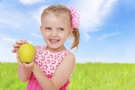 girl shows golden apple closeup.healthy food concept,active lifestyle,happiness concept,carefree childhood concept. photo