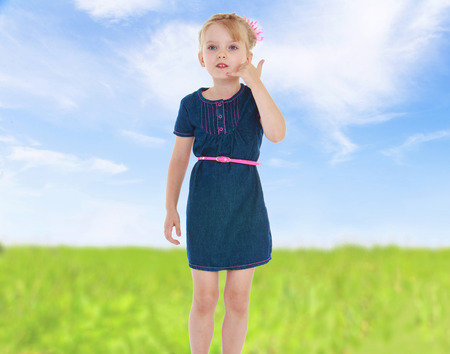 hurray: girl put her hand to her ear and shows that she wants to call.cheerful summer holiday,active lifestyle,happiness concept,carefree childhood concept.
