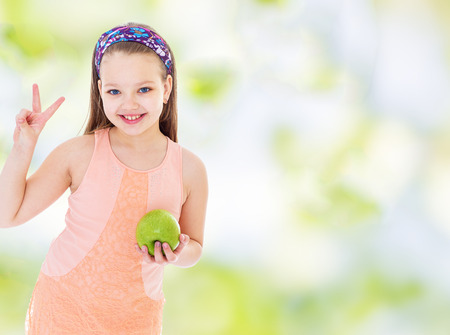 Girl showing thumbs up sign of victory and holding a green apple.healthy food concept,active lifestyle,happiness concept,carefree childhood concept. photo