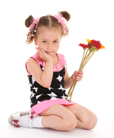 untidiness: Girl with a bouquet of flowers sitting on a white .Photo in kindergarten,active lifestyle,happiness concept,carefree childhood concept.