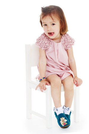 untidiness: thoughtful little girl sitting on a chair isolated white .Photo in kindergarten,active lifestyle,happiness concept,carefree childhood concept.