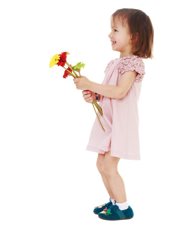 untidiness: young charming girl with a bouquet of flowers standing sideways to the camera on a white .Photo in kindergarten,active lifestyle,happiness concept,carefree childhood concept. Stock Photo