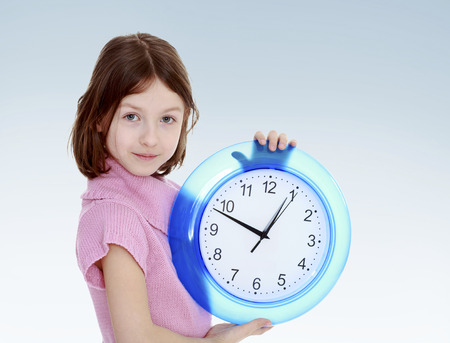 girl with a big clocknew year, warm clothing,happiness concept,happy childhood,carefree childhood,active lifestyle photo