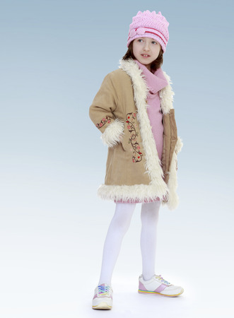 Charming little girl in a fur coat.new year, warm clothing,happiness concept,happy childhood,carefree childhood,active lifestyle photo