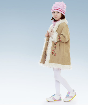girl unzips a warm coat.new year, warm clothing,happiness concept,happy childhood,carefree childhood,active lifestyle photo