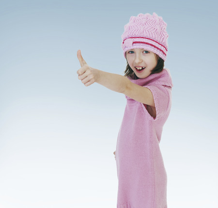 girl shows thumb.new year, warm clothing,happiness concept,happy childhood,carefree childhood,active lifestyle photo