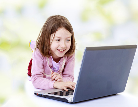 girl at the computer.technological progress, modern gadgets,happiness concept,happy childhood,carefree childhood,active lifestyle photo
