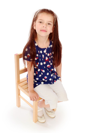 mulatto: girl sitting on a small chair.preparation for school, fun pastime,happiness concept,happy childhood,carefree childhood,active lifestyle