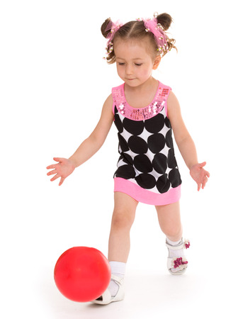 ilittle girl tosses the ballsolated on white background, sports life,happiness concept,happy childhood,carefree childhood,active lifestyle photo