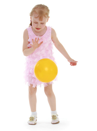 Ilittle meisje gooit de ballenolated op witte achtergrond, sportleven, gelukconcept, gelukkige jeugd, zorgeloze jeugd, actieve levensstijl Stockfoto