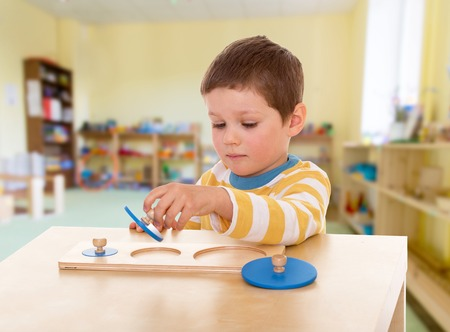 Boy engaged in the Montessori classroom kindergarten, the concept of childhood and joy, teens Archivio Fotografico