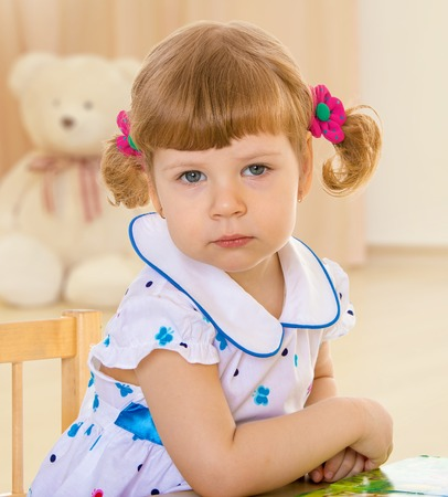 A young girl sits with her hands clasped on the table Summer fun, the concept of happiness and family wellbeing  photo