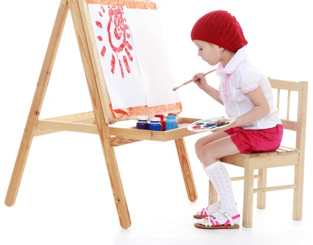 Girl artist sitting at his easel and paints the sun isolated on a white  Summer fun, the concept of happiness and family wellbeing  photo