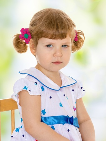 Adorable little girl is sitting on the table Summer fun, the concept of happiness and family wellbeing  photo