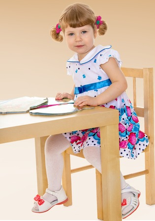 smart little girl reading a book while sitting at table Summer fun, the concept of happiness and family wellbeing  photo
