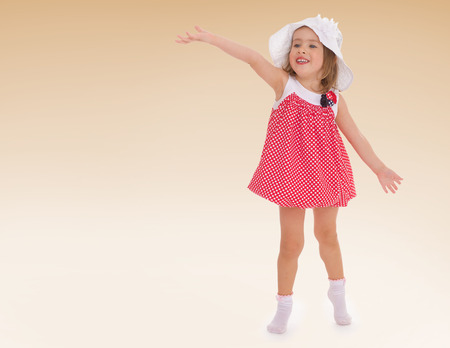 Girl summer panama hat and short dress waving  kindergarten, the concept of childhood and joy, teens photo