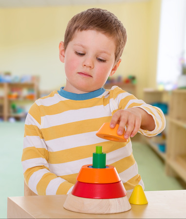 boy collects colored pyramid school Maria Montessori The concept of child development, education photo