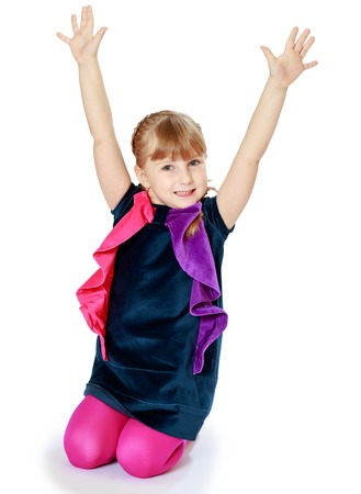 happy girl standing on her knees and understands hands up The concept of child development, education, recreation Stock Photo