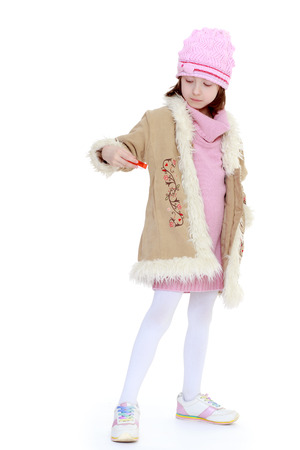 fashionable girl in warm coat on a white .The concept of a childs learning and development. photo