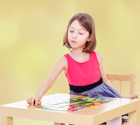 adds: Girl schoolgirl sits at a table and adds the card.