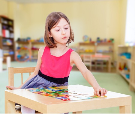 Charming girl sits at a table playing a board game.Concept of childhood and family values. photo