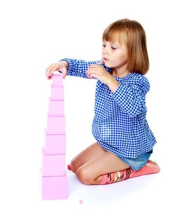 Zeer gepassioneerd meisje verzamelt Montessori pyramid.Education concept gelukkig kind.