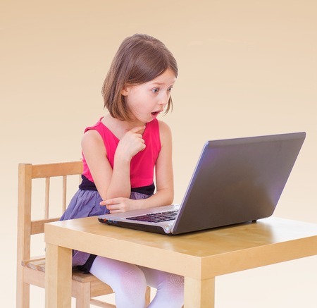upbringing: Girl sitting at the computer.The concept of development of the child, the childs upbringing.