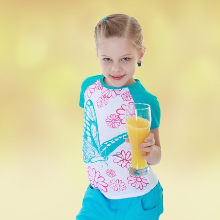 upbringing: Charming little girl drinks orange juice.The concept of development of the child, the childs upbringing.