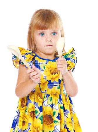 playing with spoon: girl in yellow dress plays on a wooden spoon isolated on white background.The concept of development of the child, the childs upbringing.