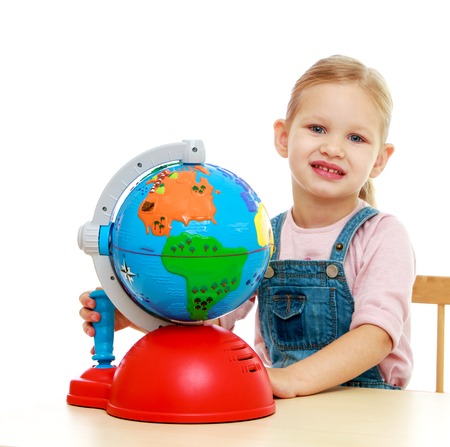 Little girl sitting at the table and looks at a globe.Childhood education development in the Montessori school concept. Isolated on white background. photo