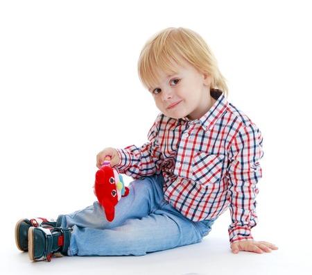 babyroom: Little boy sitting on the floor teddybear .Childhood education development in the Montessori school concept. Isolated on white background.