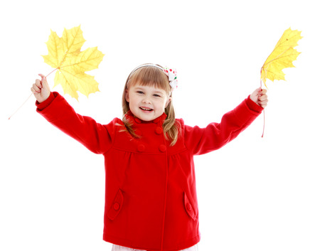 Fashionable little girl in red coat with yellow maple leaves in hands. photo