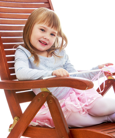 cheerful little girl is resting on a large wooden chair. Happy childhood, fashion, autumnal mood concept. Isolated on white background photo