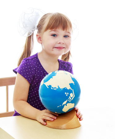 Little girl examines the globe sitting at the table. Happy childhood, fashion, autumnal mood concept. Isolated on white background photo