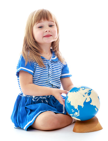 Very young little girl sitting on the floor and sees the globe. Happy childhood, fashion, autumnal mood concept. Isolated on white background photo