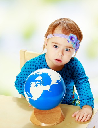 Little girl examines the globe.Happiness, winter holidays, new year, and childhood. photo
