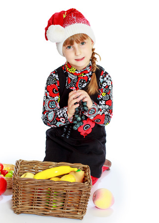 Little girl in santa claus hat ale a lesson. Happiness, winter holidays, new year, and childhood. Stock Photo