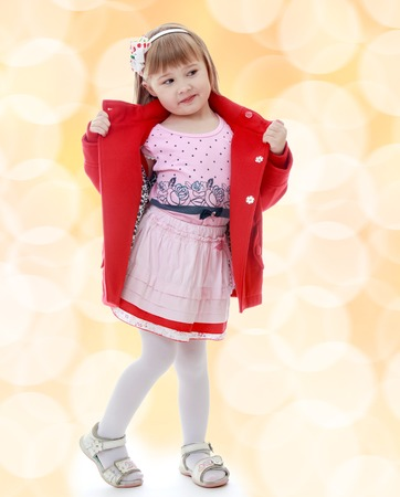 Fashionable little girl in a red coat and a pink dress.Happiness, winter holidays, new year, and childhood. photo
